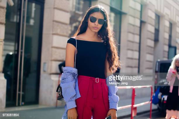 Puerto Rican model Mileshka Cortes wears black sunglasses a black offshoulder top blue striped shirt around her arms and red pants during Paris...