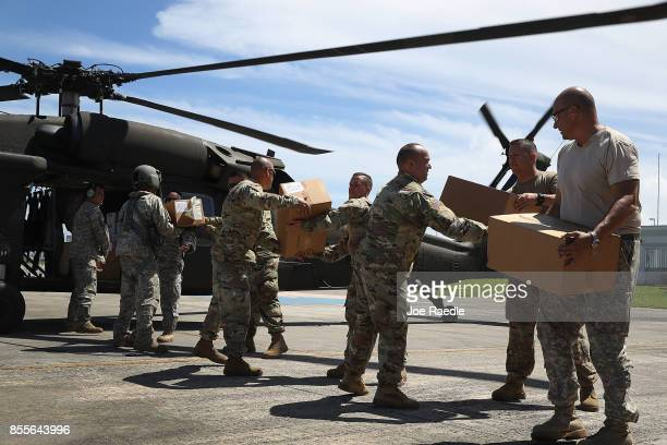 Puerto Rican National Guardsmen load a helicopter with food and water to bring to hurricane survivors as they deal with the aftermath of Hurricane...