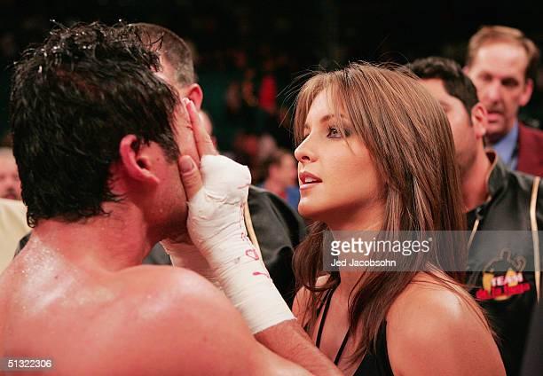 Puerto Rican pop singer Millie Corretjer talks with her husband boxer Oscar De La Hoya after he was knocked out by Bernard Hopkins for the world...