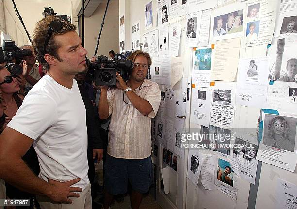 Puerto Rican pop star Ricky Martin looks at notices of missing person while touring the damage area caused by the tsunami disaster at Kamala beach in...