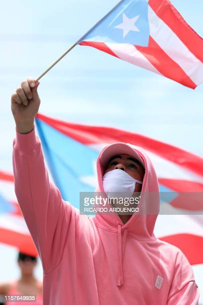 Puerto Rican rapper Bad Bunny participates in a march the day after the governor of Puerto Rico Ricardo Rossello resigned from his charge in San Juan...
