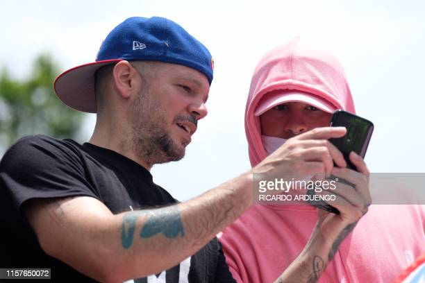 Puerto Rican rappers Rene Perez Residente and Bad Bunny participate in a march the day after the governor of Puerto Rico Ricardo Rossello resigned...