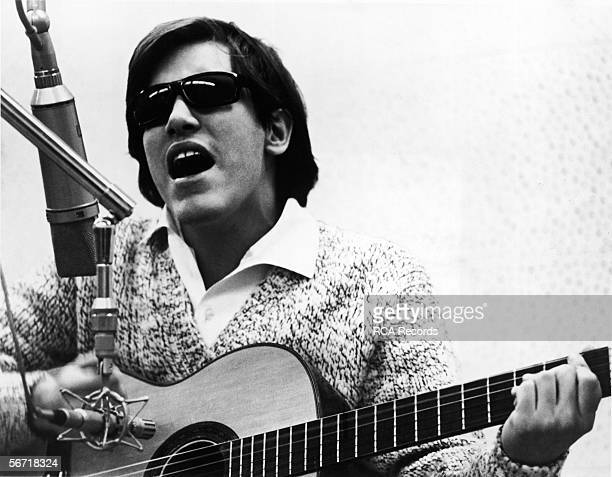 Puerto Rican singer and musician Jose Feliciano performs in front of microphones in a recording studio late 1960s or early 1970s