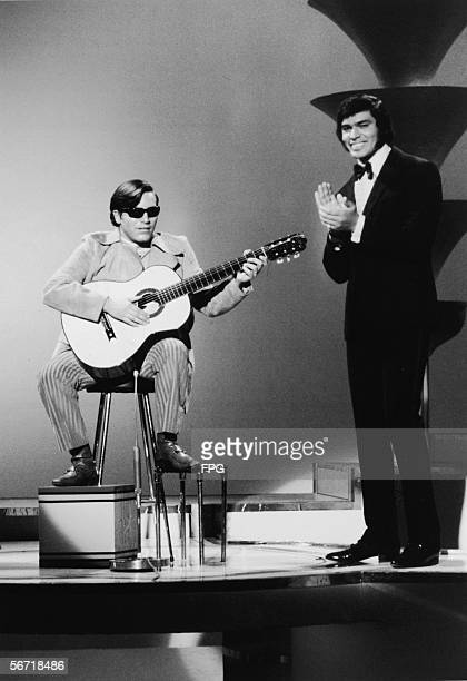 Puerto Rican singer and musician Jose Feliciano performs on stage in a television show his perfomance enjoyed by a tuxedoclad host who stands nearby...