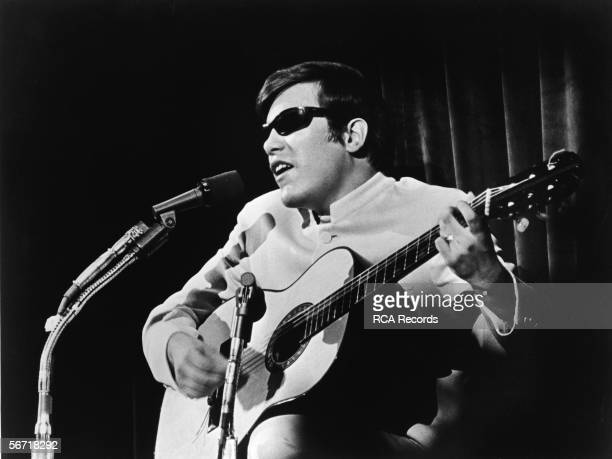 Puerto Rican singer and musician Jose Feliciano performs with a guitar in front of a microphone late 1960s or early 1970s