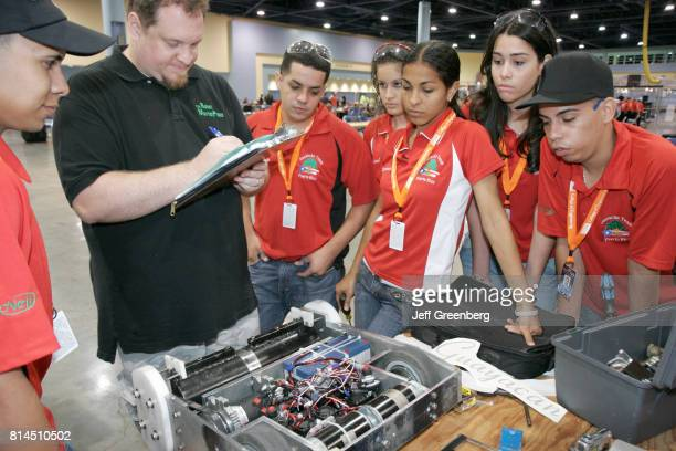 Puerto Rican students and a judge looking at their battle robot for the National Robotics Competition