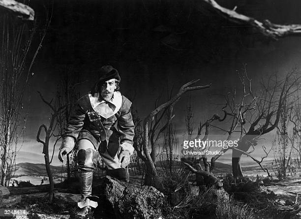 Puerto Ricanborn actor Jose Ferrer crouches while walking through trees and bramble at night in a still from the film 'Cyrano de Bergera' directed by...