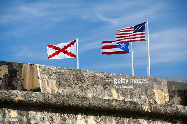 puerto rico, old san juan, el morro fortress, flags behind wall - old san juan wall stock photos and pictures