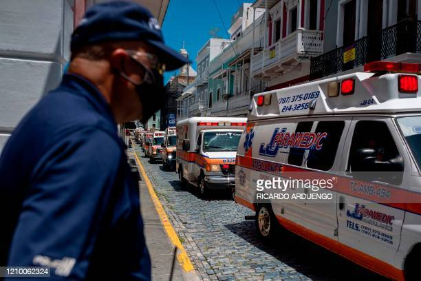 Puerto Rico police officers stand in front of the governor's mansion as hundreds of private and municipal paramedics protest in their ambulances...