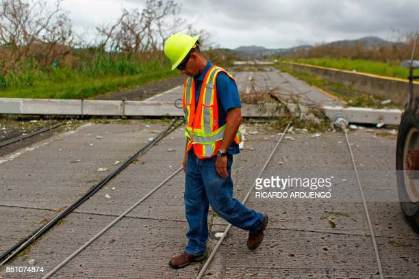 A Puerto Rico Power Authority worker walks between downed power lines in the aftermath of Hurricane Maria in Luquillo Puerto Rico Thursday September...