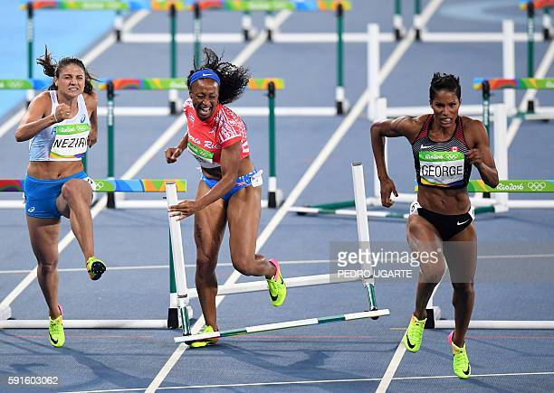 TOPSHOT Puerto Rico's Jasmine CamachoQuinn misses a hurdle while competing with Finland's Nooralotta Neziri and Canada's Phylicia George compete in...