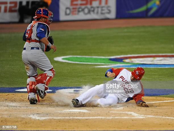 Puerto Rico's Michael Aviles slides into home for the score as Panama's catcher Carlos Ruiz awaits a throw during the Pool D game two between the...