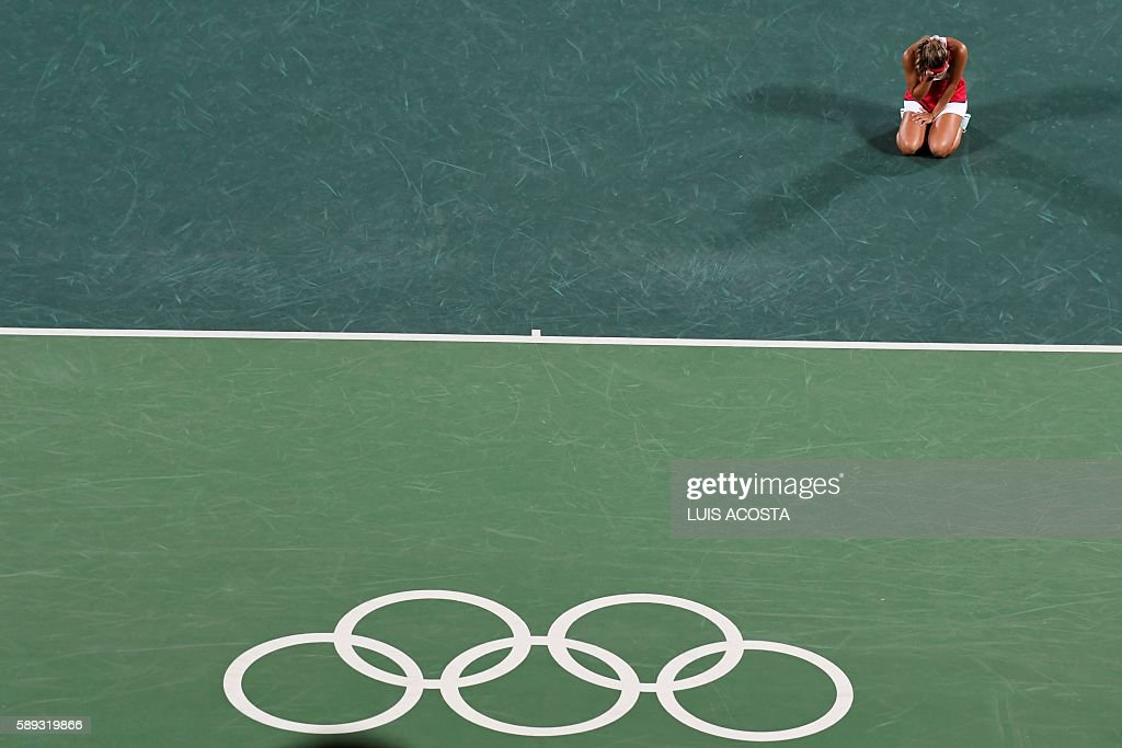 TOPSHOT - Puerto Rico's Monica Puig reacts after winning her women's singles final tennis match against Germany's Angelique Kerber at the Olympic Tennis Centre of the Rio 2016 Olympic Games in Rio de Janeiro on August 13, 2016. / AFP / Luis Acosta