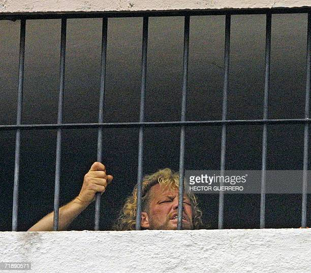 In this 19 June 2003 file photo US bounty hunter Duane 'Dog' Chapman peers through the bars of the police station in Puerto Vallarta in Mexico...