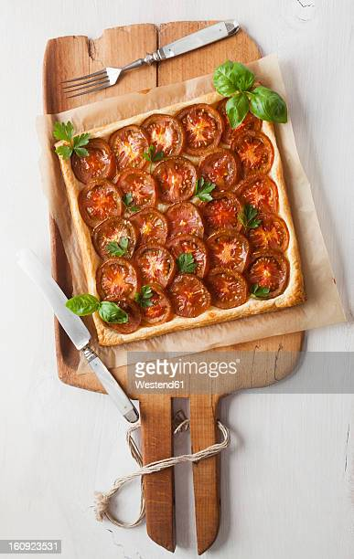 Puff pastry tarte garnished with tomato slices and herb on chopping board