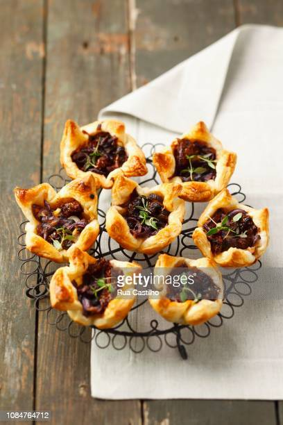 puff pastry tartlets with sundried tomatoes, caramelised onions and thyme - rua stock-fotos und bilder