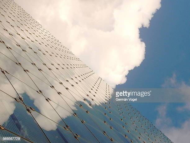 Puffy cloud collides & reflects on building glass