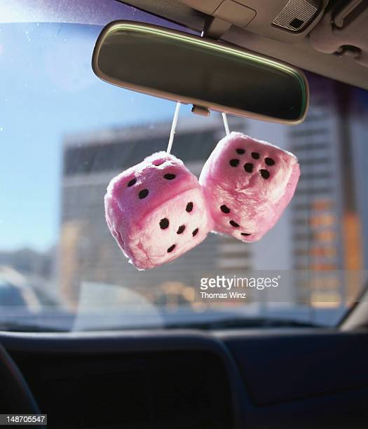 Puffy dice hanging from rear view mirror.