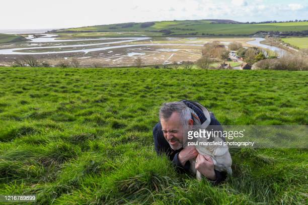 "pug licking mans face at cuckmere haven - ""paul mansfield photography"" stock pictures, royalty-free photos & images"