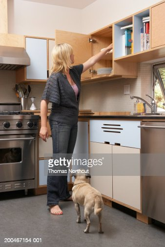 Pug Standing Beside Woman Reaching Into Kitchen Cabinet