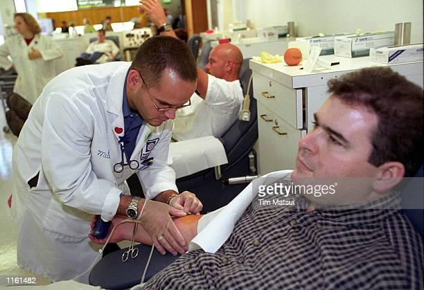 Puget Sound Blood Center employee Mitch Feller draws blood from Seattle resident Zander Batchelder September 11 2001 as the citizens of Seattle...