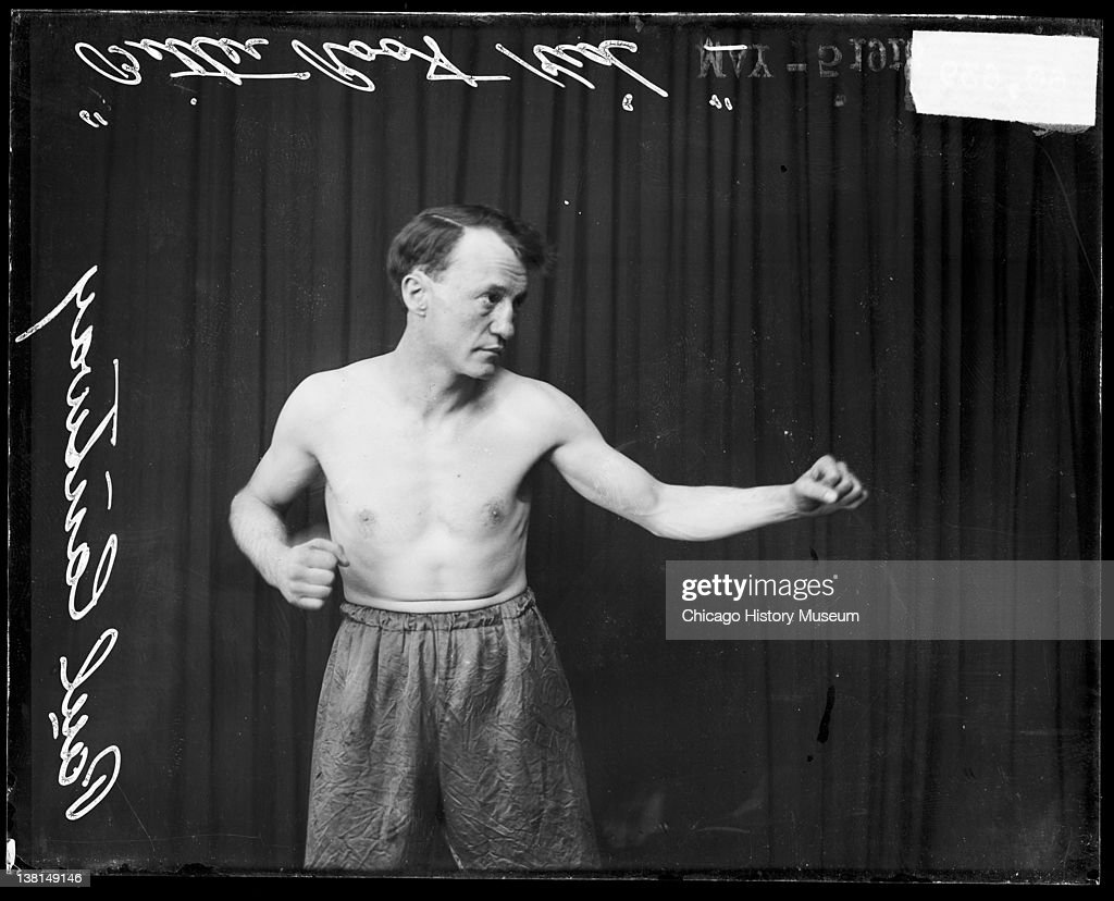 Pugilist, Bitter Root Kid, standing in a boxing stance in front of a dark backdrop, Chicago, Illinois, 1916. From the Chicago Daily News collection.
