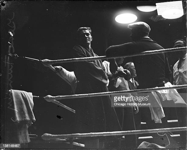 Pugilist Gene Tunney surrounded by a group of men standing in a corner of a boxing ring before a bout against Jack Dempsey at Soldier Field Chicago...