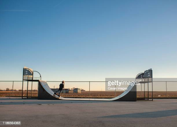 pullback of boy riding half pipe ramp on hoverboard against blue sky - half pipe stock pictures, royalty-free photos & images
