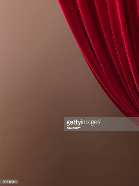 A pulled red velvet curtain with a tan wall