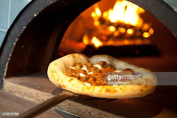 Pulling butternut squash pizza from wood fire oven