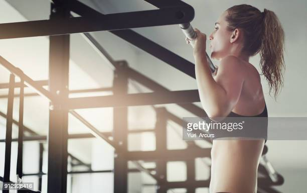 pulling herself up - chin ups stock photos and pictures