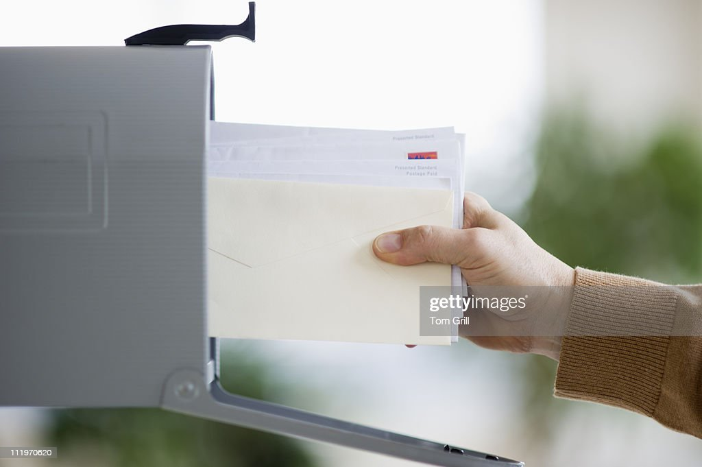 pulling mail out of mailbox : Foto de stock