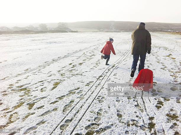 pulling sledde uphill - taken on mobile device stock photos and pictures