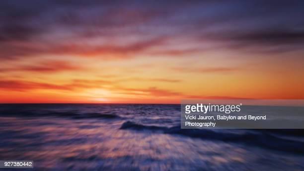 Pulling Waves Against Orange Sunrise