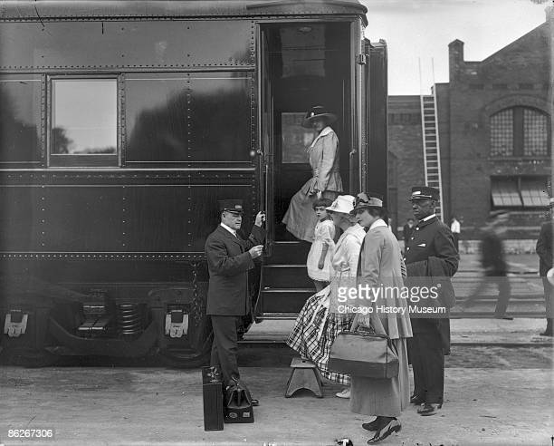 A Pullman porter assists a woman and child in boarding the train Chicago IL ca1915 Chicago served as America's rail capital during the Great Age of...