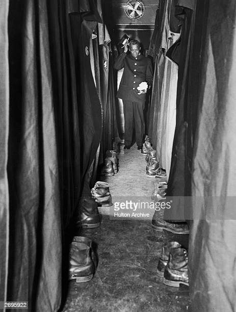 Pullman porter at the end of a train car corridor scratches his head and holds show polish and cloths as he contemplates the pairs of shoes arrayed...