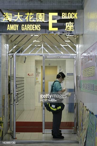 Hong Kong City Of Fear. HONG KONG principal foyer du Syndrome respiratoire aigu sévère : facteur distribuant le courrier dans l'entrée du bloc E de...