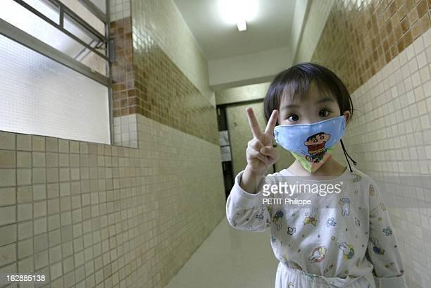 Hong Kong City Of Fear. HONG KONG principal foyer du Syndrome respiratoire aigu sévère : Lam TSANG 3 ans, faisant le V de la victoire, en pyjama dans...