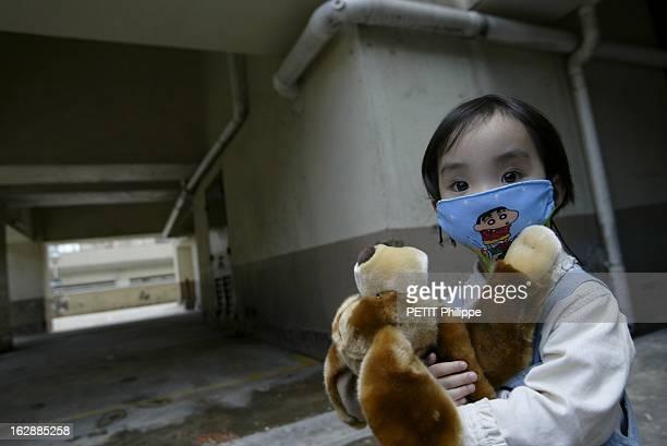 Hong Kong City Of Fear. HONG KONG principal foyer du Syndrome respiratoire aigu sévère : Lam TSANG 3 ans, portant un masque, serrant dans ses bras sa...