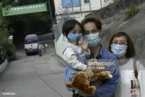 Hong Kong City Of Fear. HONG KONG principal foyer du Syndrome respiratoire aigu sévère : Lam TSANG 3 ans et ses parents, tous trois portant un masque...