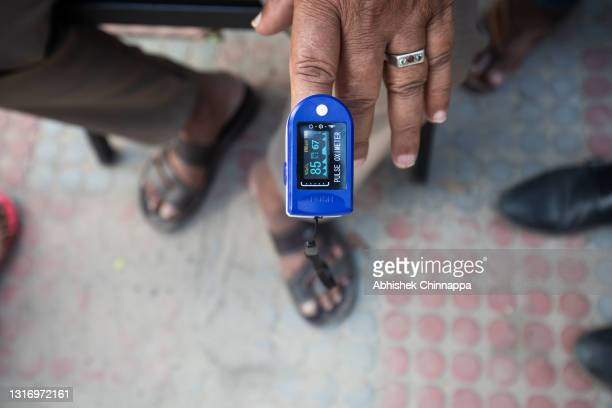 Pulse oximeter reading is seen on the finger of Subramanya P as he struggles to breathe with the aid of supplemental oxygen provided by an NGO on a...