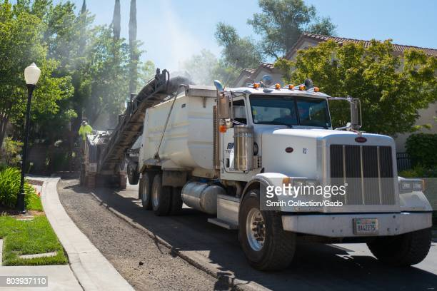 Pulverized asphalt pours from a conveyor into a dump truck releasing a cloud of dust during a road construction and resurfacing project in the San...