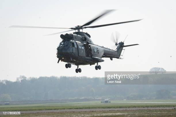 Puma HC2 helicopter comes into land as members of the UK Armed Forces work with NHS medical staff and Air Ambulance Service crews at Thruxton...