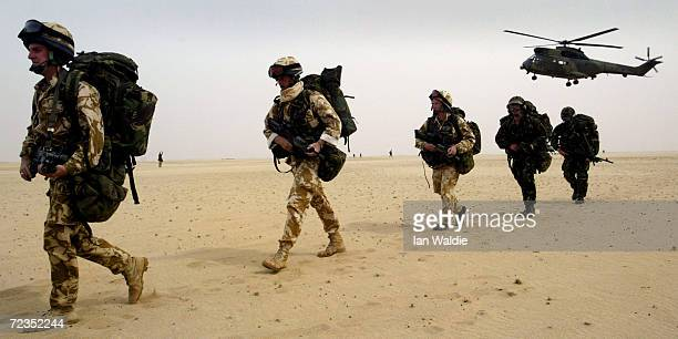 Puma helicopter from the Joint Helicopter Force hovers as troops from 51 Squadron Royal Air Force Regiment march through the desert March 11, 2003 in...