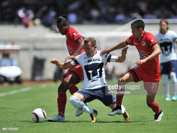 Pumas' Abraham Gonzalez vies for the ball with Lobos Buap's Pedro Aquino and Eduardo Tercero during their Mexican Torneo Apertura 2017 football match...