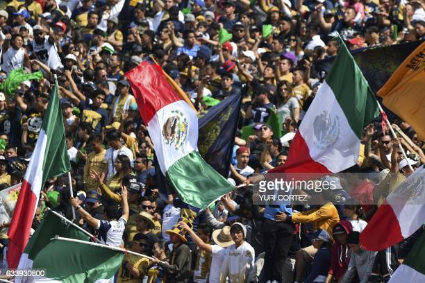 Pumas' fans flutter the Mexican national flag as part of a nationalism campaign regarding US President Donald Trump's plans of building a wall...