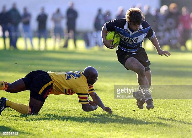 Pumas fullback Federico Serra jumps over a diving Paul Joseph during the Argentinans second tour match at Paeroa Tuesday Argentina 26 Thames Valley 12