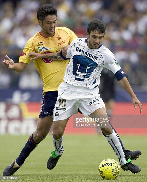Pumas' Ignacio Scocco vies for the ball with Morelia's Horacio Cervantes during their Mexican league football match in Mexico City on March 9 2008...