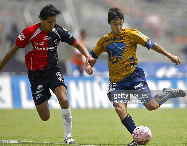Pumas player Ignacio Scocco vies for the ball with Atlas player Hugo Ayala during their Mexican League football match in Mexico City 30 September...