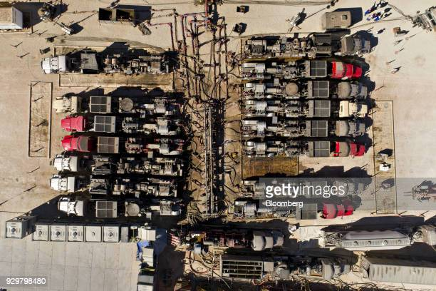Pump trucks feed into a network of pipes near six Chevron Corp oil wells being readied for hydraulic fracturing in the Permian Basin in this aerial...